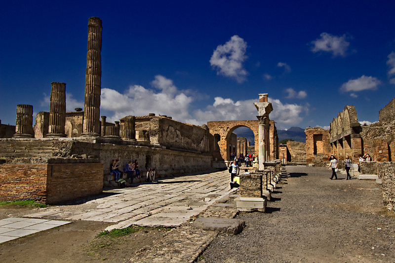 Temple of Jupiter and honorary arch form one end of the Forum in Pompeii. Lurking in the background is Mount Vesuvius, with its blown-off top, which erupted in 79 AD and buried the town in ash.