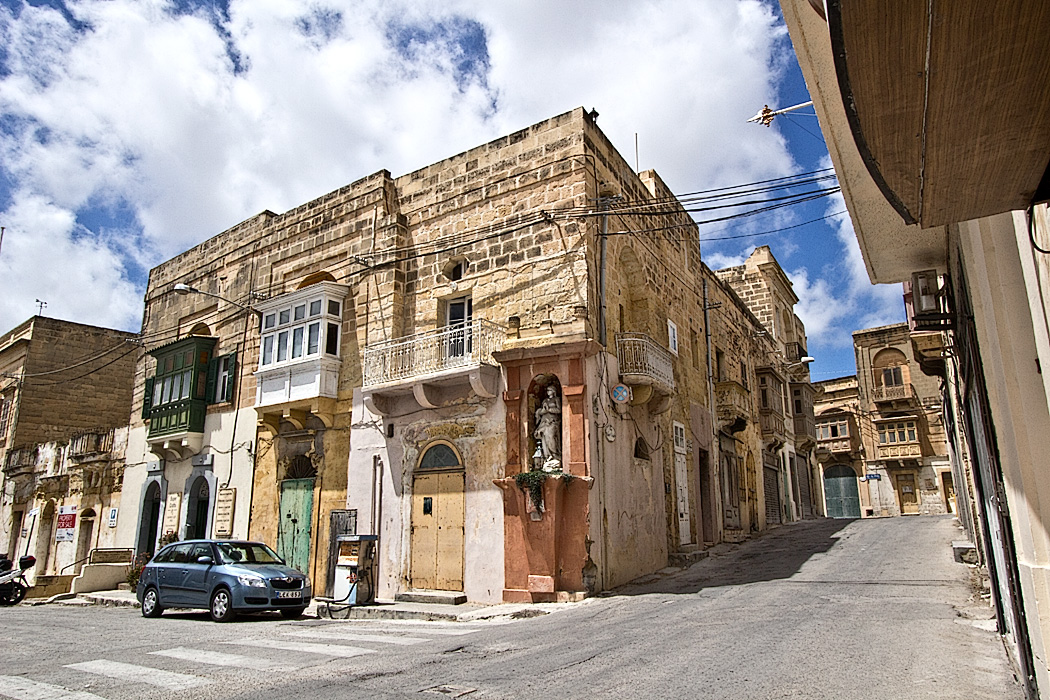 Historic limestone buildings on the island of Gozo feature decorative wooden balconies, an architectural feature from the days of Arab occupation in the Maltese Islands