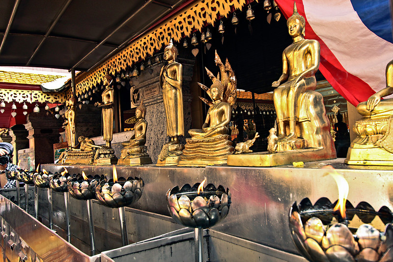 Flames stand sentinel before an array of Buddhas at Doi Suthep Temple in Chiang Mai, Thailand