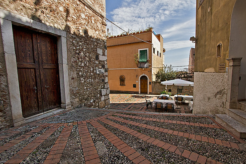 Beautiful street scenes like this one, where hand-laid bricks create a sunburst pattern at the entrance to Varo Church, are the norm in Taormina, Sicily, Italy
