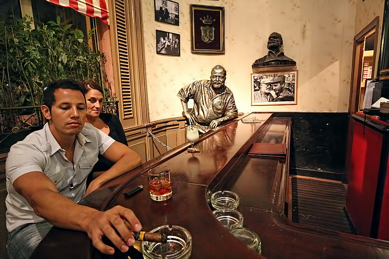 Bronze sculpture of Ernest Hemingway stands at the end of the bar in La Floridita, one of his favorite watering holes