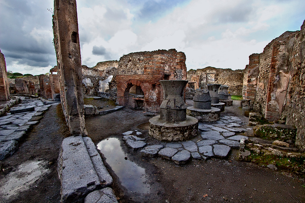 Ruins of large bakery at Pompeii, Italy, with remains of exterior wall and street leading up to the shop