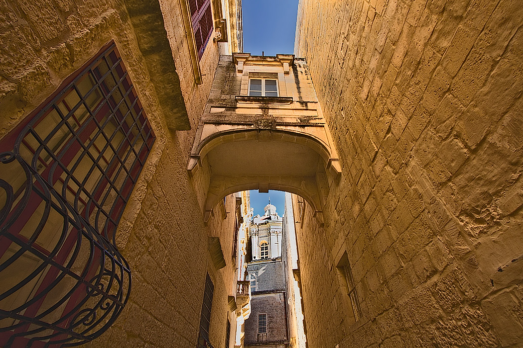 Stone bridge between buildings frames St. Paul's Cathedral in the old walled city of Mdina on the island of Malta