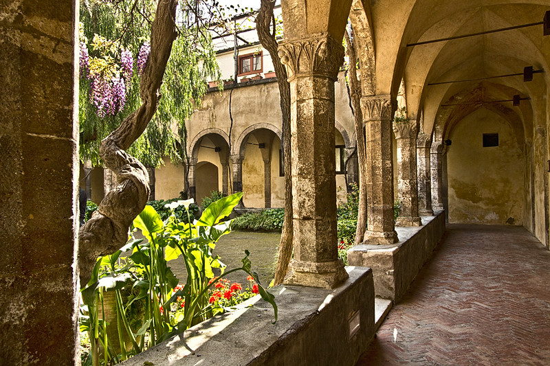 Gothic columns surround a peaceful garden at the Cloister of St. Francis in Sorrento, Italy