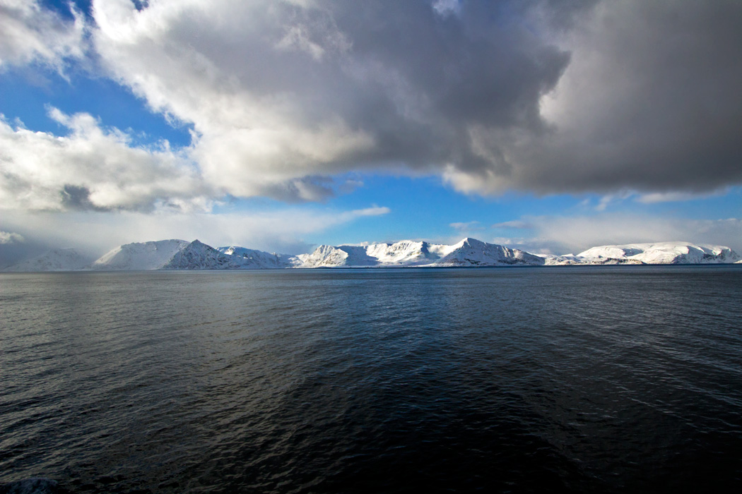 Ultramarine seas and snow-dusted rocks above the Arctic Circle, near Hammerfest, Norway