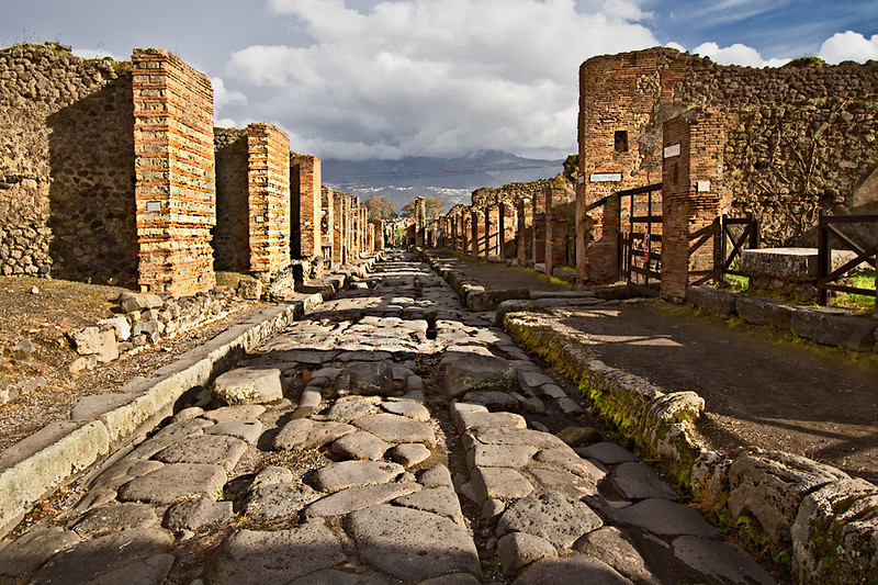 Typical Pompeii street with wheel ruts carved deeply into the stone pavement.