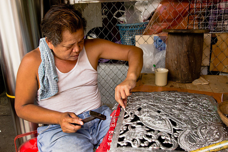 Worker cuts elaborate designs into sheets of aluminum in Chiang Mai, Thailand