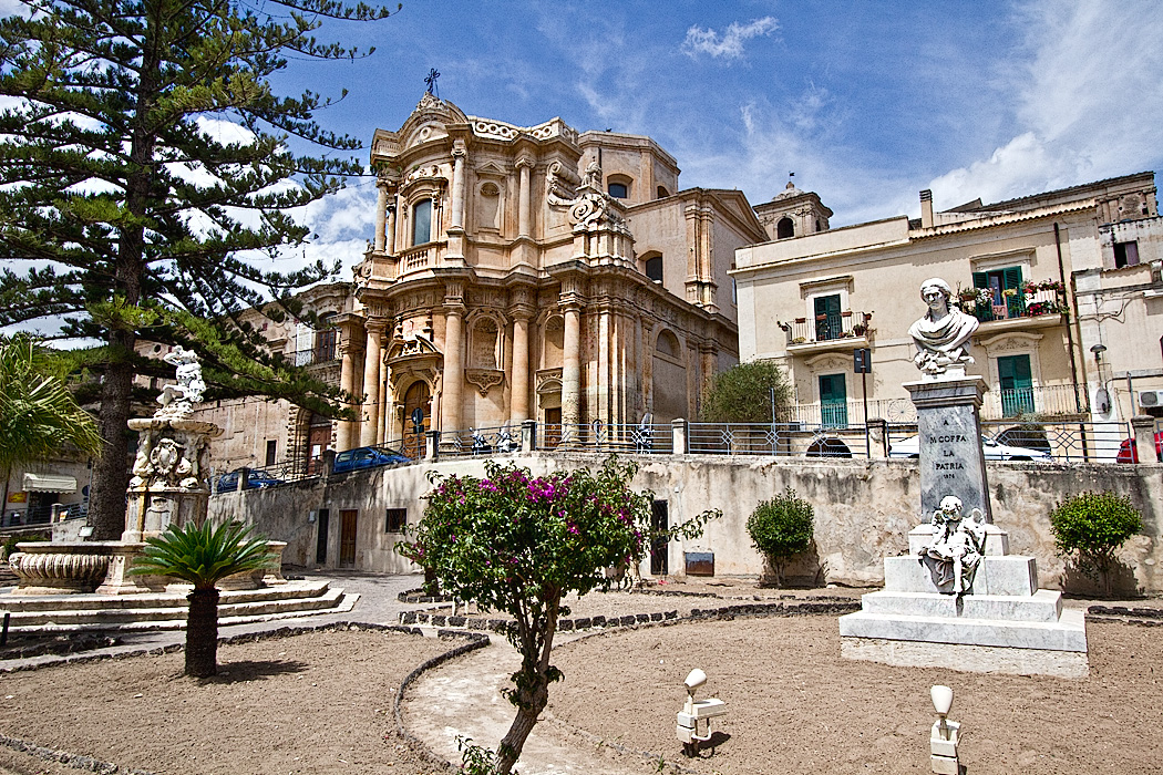 Church of San Domenico and magnificent Fountain of Hercules are the centerpieces of Piazza XVI Maggio, located near the western end of Corso Umberto Vittorio, the main thoroughofare in the Baroque town of Noto, Sicily.