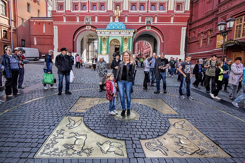 """Visitors at the entrance to Red Square toss coins while standing on """"Zero Kilometer,"""" the place from which all distances in Moscow are measured."""