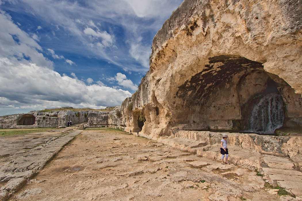 The Nymphaeum, or Grotto of the Nymph, an artificial cave carved into the limestone cliffs above the ancient Greek Amphitheater in Syracuse, Sicily. An aqueduct carried water into the grotto from miles away and both the cave and niches in the cliff were once embellished with statues of religious images.