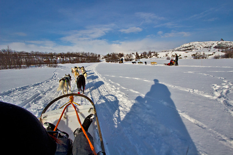 Husky teams pull two passengers dogsleds through a pristine white landscape in Kirkenes Norway
