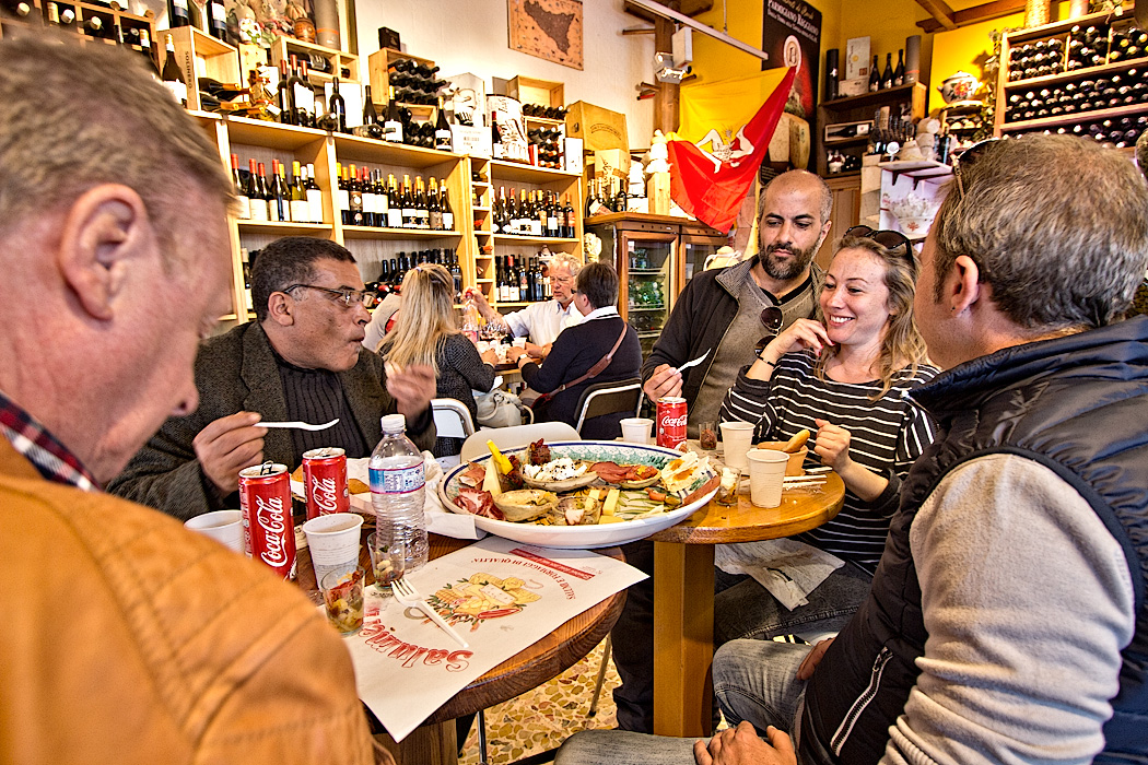 Family shares a huge platter of Antipasti at a local shop and cafe in the Ortigia (Old Town) area of Syracuse, Sicily, Italy, where the morning market sells fresh produce and seafood every morning