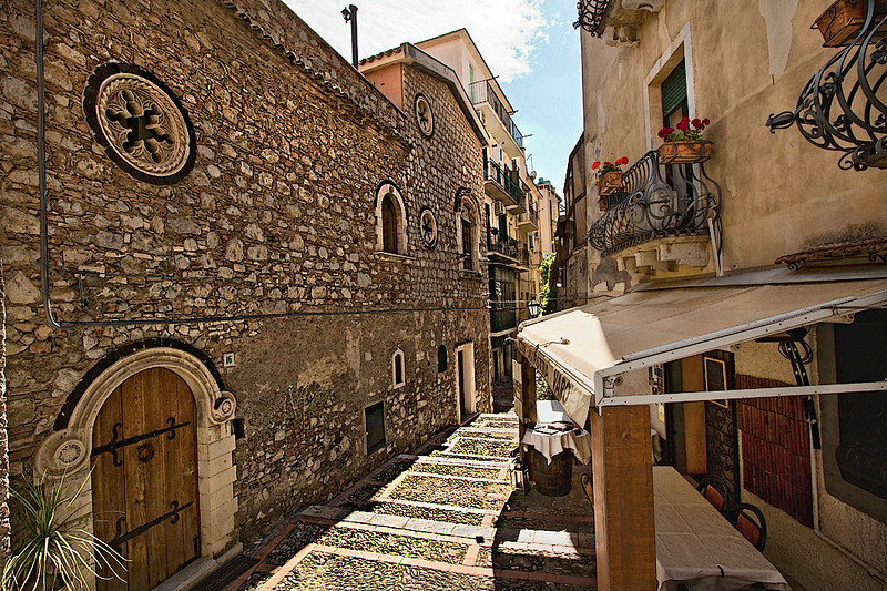 Typical street in Taormina, Sicily is paved with cobblestones and lined with lovingly restored builings