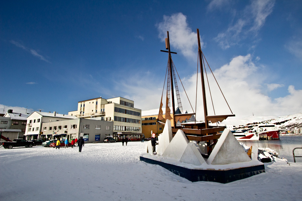 Sculpture of wooden sailing vessel dominates snowy harborfront in Hammerfest, Norway