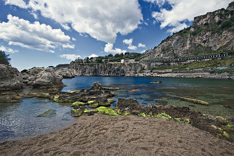 View of the coastal highway and cliffs of the town of Taormina, Sicily, from Isola Bella Island, which can be reached via a spit of sand at low tide
