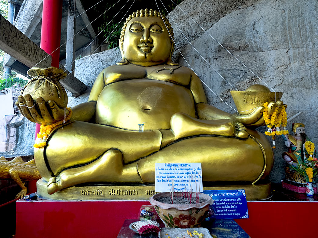 Slipping an offering into the slot in the belly of this giant seated Buddha at Khao Tao temple in Hua Hin, Thailand is said to bring the donor good luck