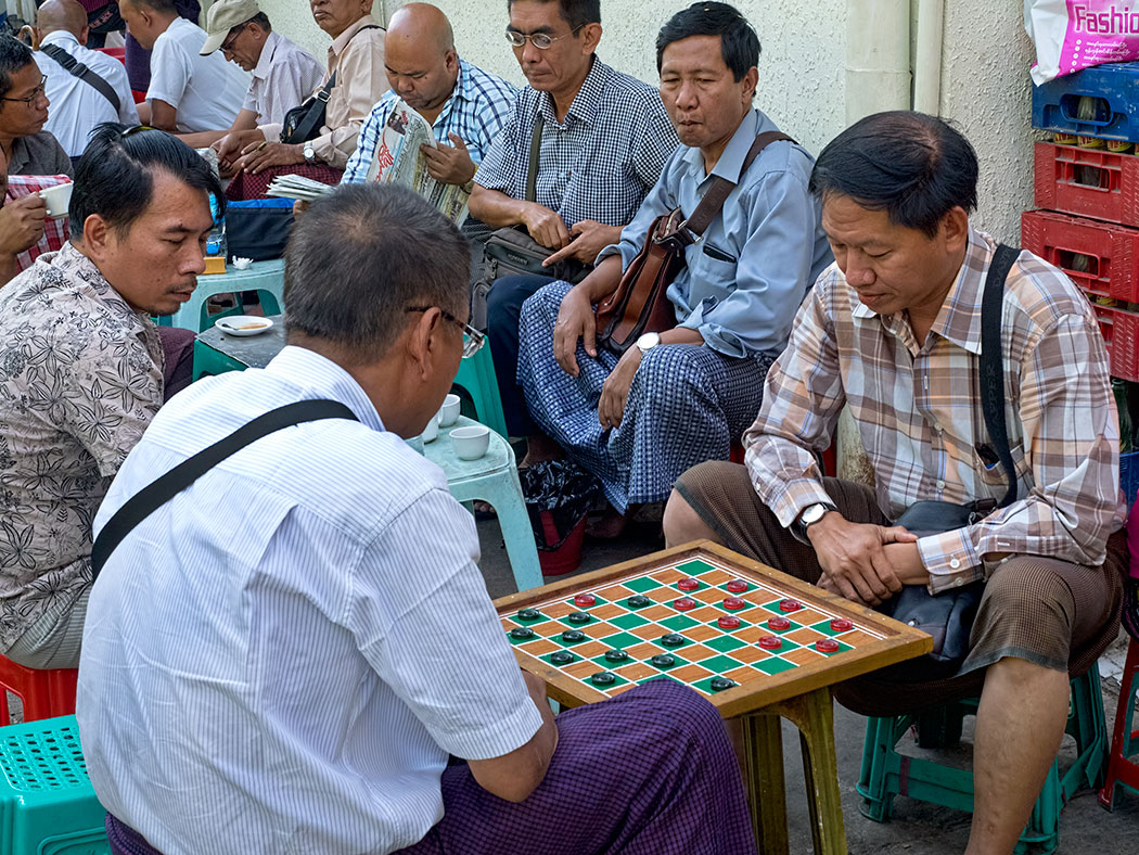 Men in Yangon, Myanmar break for tea and checkers every afternoon, squatting on low plastic stools that are set out on the streets