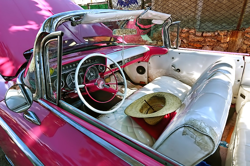 A quintessential classic Cadillac, painted an eye-popping hot pink, sits on the streets of Old Havana, Cuba
