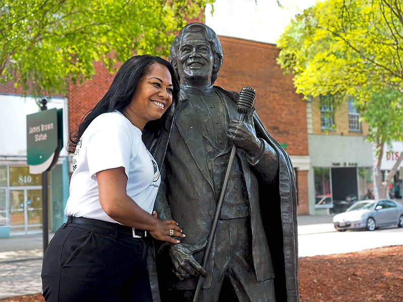 Deanna Brown-Thomas poses in downtown Augusta with the statue of her father, James Brown