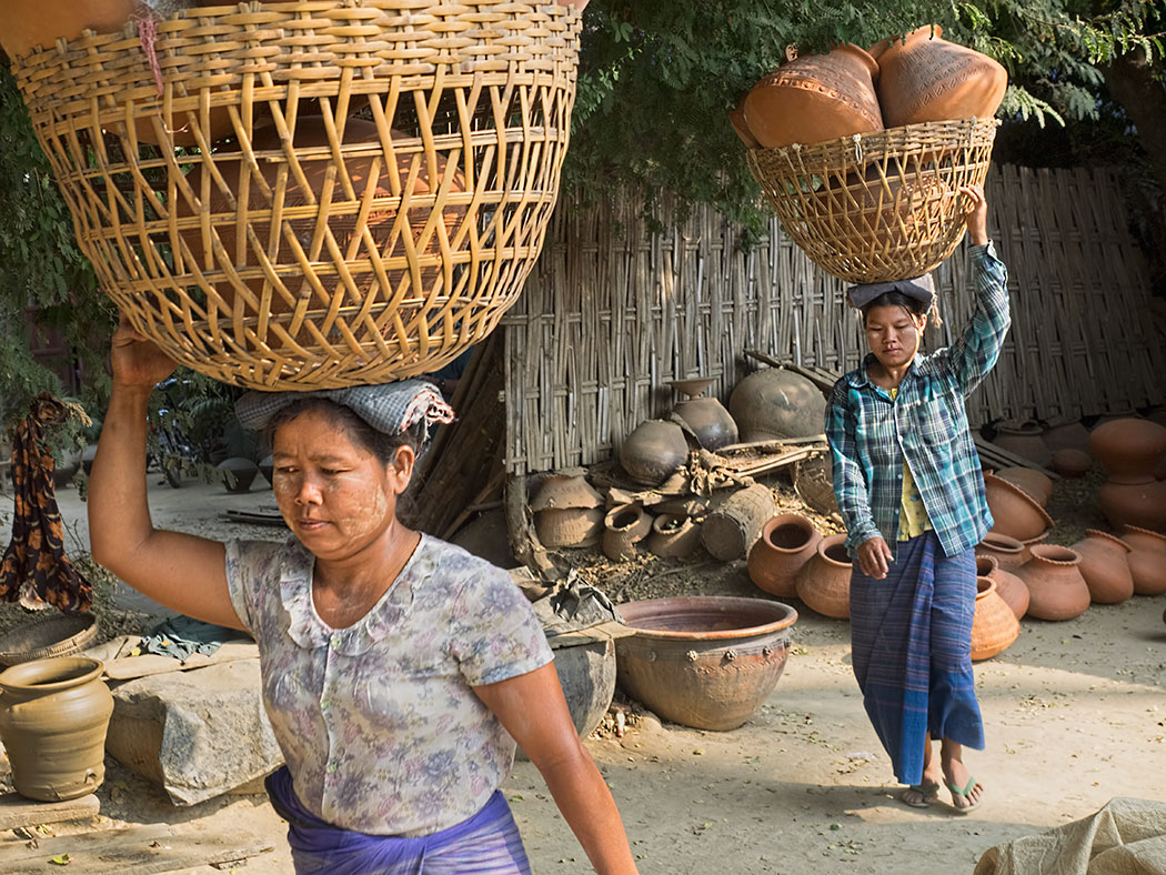 Women from Yandabo pottery making village near Mandalay, Myanmar, carry freshly fired pots down to the riverbank in preparation for shipping