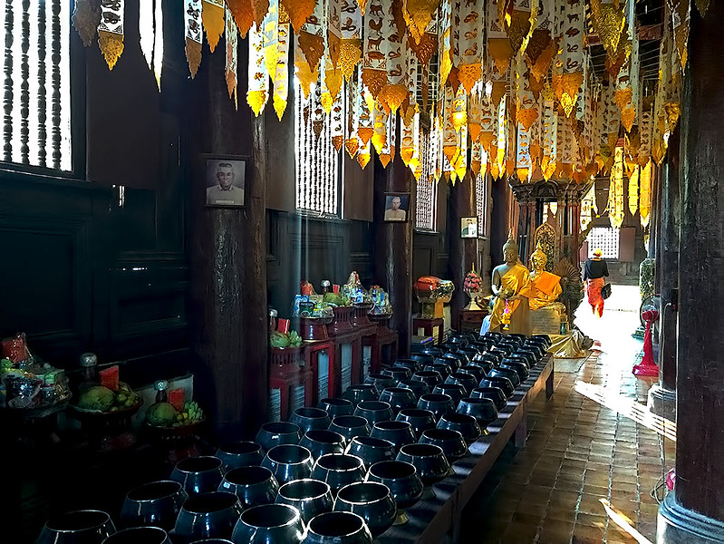 Buddhists earn merit by dropping small coins in each of the 108 black bowls at Wat Pan Tao in Chiang Mai, Thailand