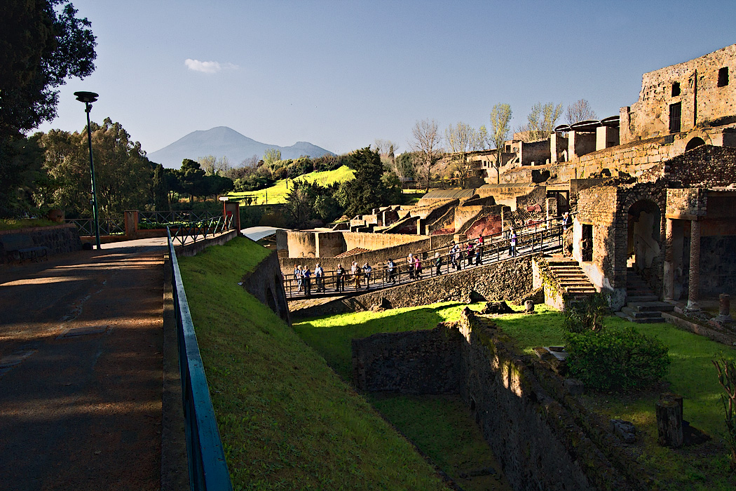 View of the entrance to the ruins of Pompeii, Italy, with unexcavated hills and Mount Vesuvius in the background.