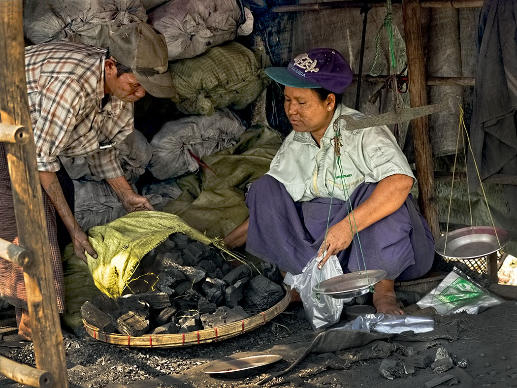 Unloading charcoal to be sold at the market in Dala, a small village across the river from downtown Yangon, Myanmar