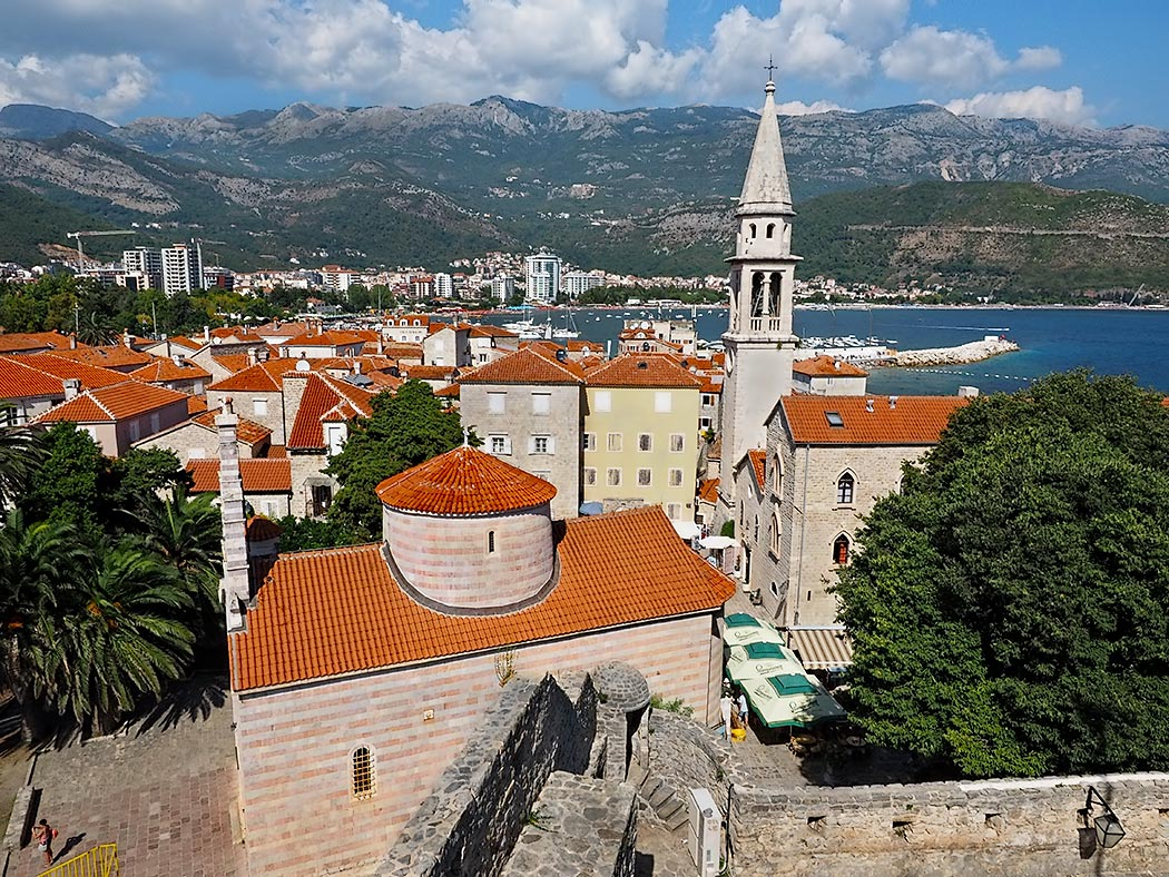 Medieval walled city of Budva, Montenegro, as seen from the Citadel, with the Church of the Holy Trinity in the foreground, and the bell tower of the 7th century Church of St. John, the highest structure in the town