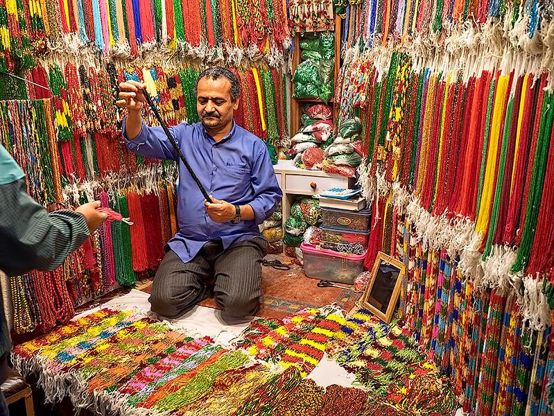 Shop owner strings a custom necklace in the Pote Bazaar (bead market) area of Indra Chowk in Kathmandu, Nepal
