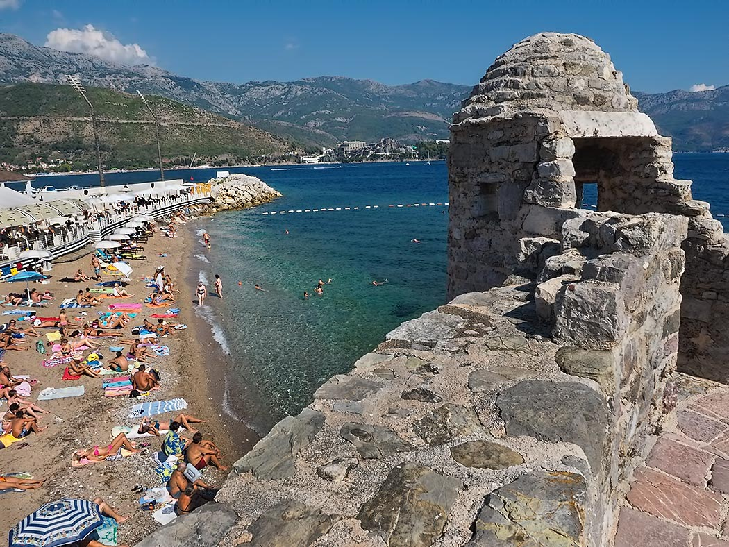 Sun worshipers flock to Pizana Beach on the shores of the Adriatic Sea in Budva, Montenegro. Though small, it is one of the more popular beaches, as it is wedged into a protected cove between the walls of the old city and Dukley Beach Club.
